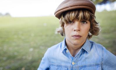 Portrait of serious looking blond boy wearing cap
