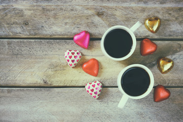 top view image of colorful heart shape chocolates, fabric heart and couple mugs of coffee on wooden table. valentine's day celebration concept