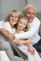 Portrait of senior couple with granddaughter on sofa in living room