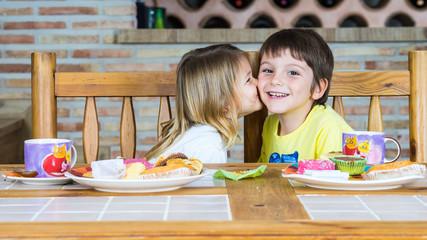 Pareja de hermanos, la niña besa al niño