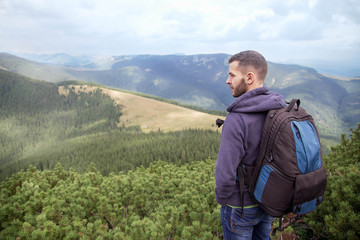 Outdoor portrait of Young man hiking   on the mountains,smiling happy   portrait of tourist male. Travel bag,   caucasian Male hiker walking in forest