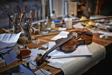 Tools and damaged instruments in a violin maker's workshop