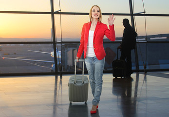 Young woman with suitcase in hall of airport