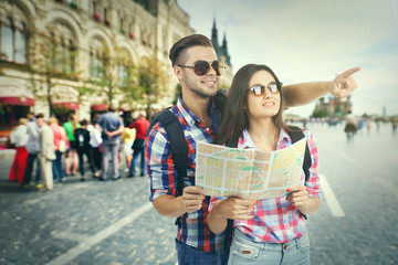 Happy tourists with map on street in city