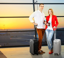Young couple with suitcases in hall of airport