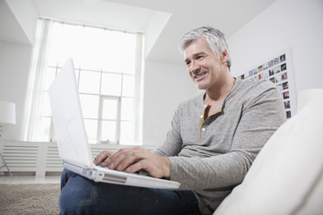 Germany, Bavaria, Munich, Mature man using laptop on couch, smiling