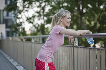 Germany, North Rhine Westphalica, Duesseldorf, Young woman leaing on railings