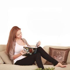 Frau liest Magazin auf dem Sofa