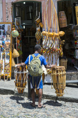 Brazilian street performer walks with rustic pair of drums in the Pelourinho historical district of Salvador, Bahia, Brazil