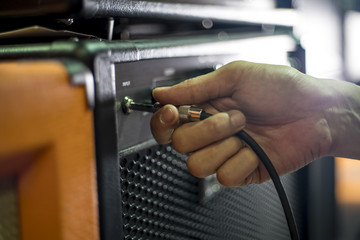 Closed up hand holding jack plug-in to the guitar amplifier