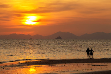 Silhouetted of couple, sweet in the beach at Krabi, Thailand.