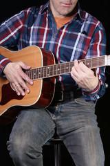 Musiker spielt Konzertgitarre, schwarzer Hintergrund
