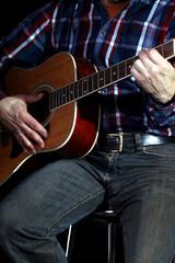 Musiker spielt Gitarre, dunkler Hintergrund