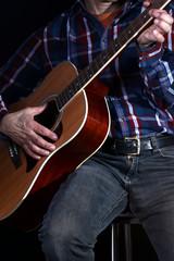 Musiker zieht Gitarre hoch, spielt