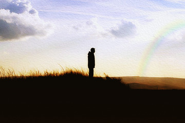 Meditation. Boy standing on top of a hill over the rainbow