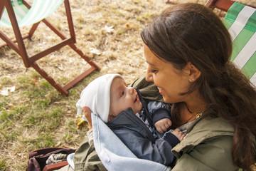 Bella e dolce mamma allatta il bambino in un parco di Londra