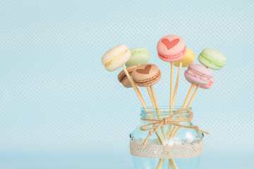 Colorful macaroons on wooden sticks in a glass jar