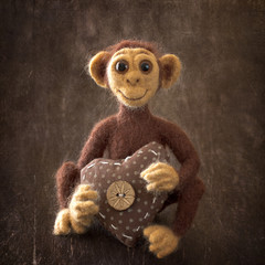 New Year 2016 the year of the monkey . Homemade toy monkey with a heart on a brown background with a texture .