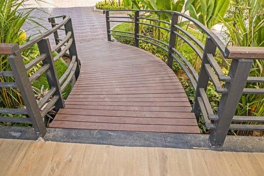 Sloping wooden boardwalk viewed as walking in garden