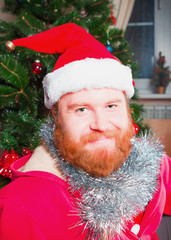 A bearded man in a red suit of Santa Claus smiling