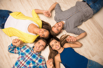 Cheerful young people lying on the floor holding hands