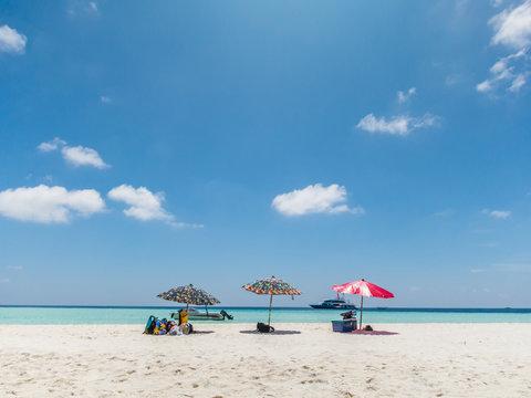 Colorful beach umbrella, white beach and blue sky