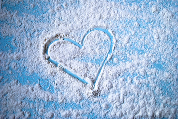 Heart image on a scattered flour on a light blue surface