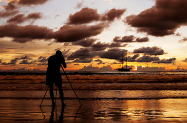 Silhouette photographer shooting image on the beach