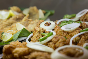 fried fish with onion and pepper, selective focus on central.