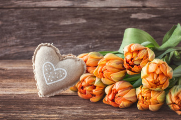 Bouquet of tulips and heart on wooden background. Toned, copy space