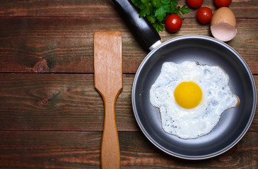Aluminium Prints Egg Pan of fried eggs, with cherry-tomatoes and parsley on a wooden table surface