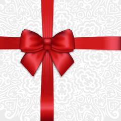 Shiny holiday red satin ribbon bow on white lacy ornamental  bac