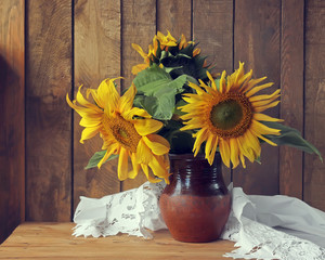 Still life with a bouquet of sunflowers in a clay jug.