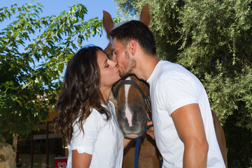 Young couple kissing in front of a brown horse.