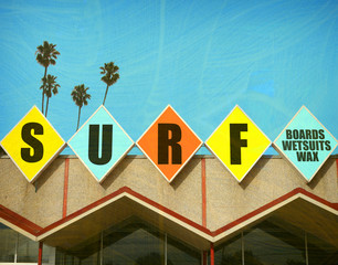 aged and worn vintage photo of surf sign with palm trees