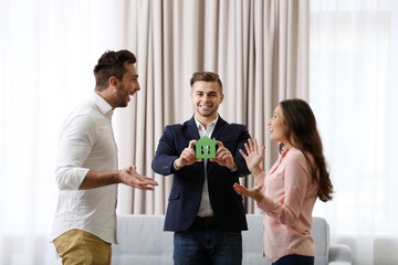 Estate agent with model of house and happy couple on home interior background