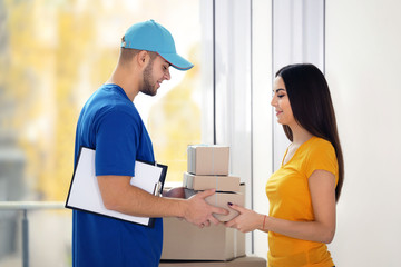 Receiving parcel - delivery man gives package to young woman