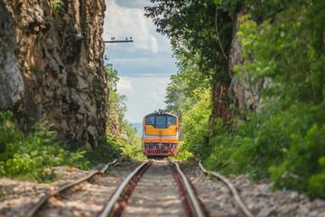Train runs through a narrow gorge in the valley.