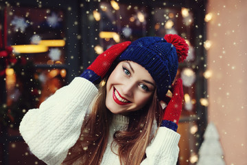 Street portrait of smiling beautiful young woman wearing classic winter knitted clothes. Model looking at camera, Festive  garland lights. Magic snowfall effect. Close up. Toned