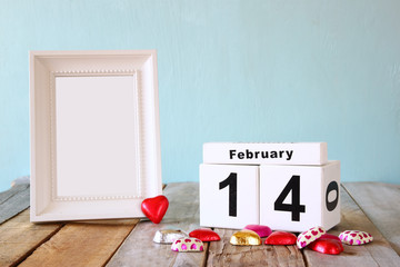 February 14th wooden vintage calendar with colorful heart shape chocolates next to blank vintage frame on wooden table. selective focus.Template ready to put photography