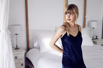 Stunning young woman wearing camisole in bedroom