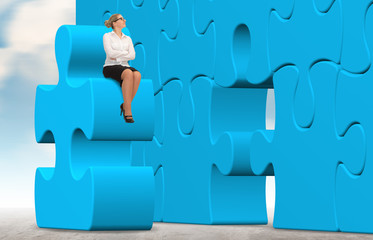 business woman building a blue puzzle on a sky background