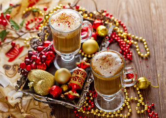 two cups of hot coffee or a cappuccino with Christmas decorations