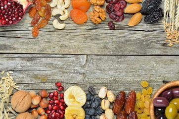Dried fruits, barley, wheat, olives, pomegranate on a wooden table - symbols of judaic holiday Tu Bishvat .Copyspace background. Top view