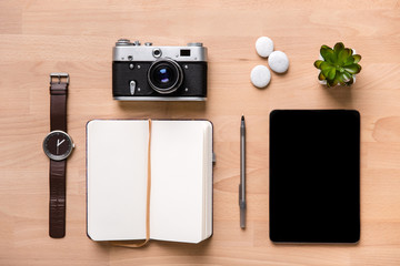 Opened blank notepad, pen, watch, vintage camera, tablet and flower