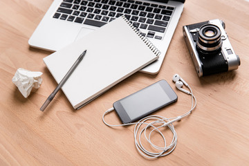Laptop, vintage camera, mobile phone, earphones and notebook with pen
