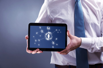 Businessman holding tablet-pc with social network structure on screen