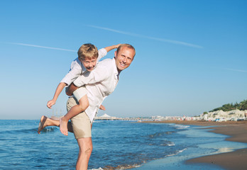 Father with son playing on the sea side