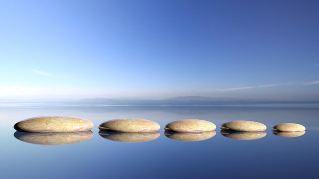 Zen stones row from large to small  in water with blue sky and peaceful landscape background