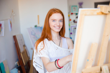 Cheerful attractive woman artist painting on canvas in art workshop